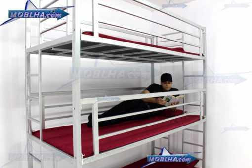 شخصی در حال مطالعه بر روی تخت خواب سه طبقه